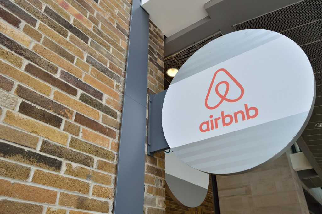 "A round white sign affixed to a brick wall has the orange Airbnb logo and reads ""airbnb"" in orange text."