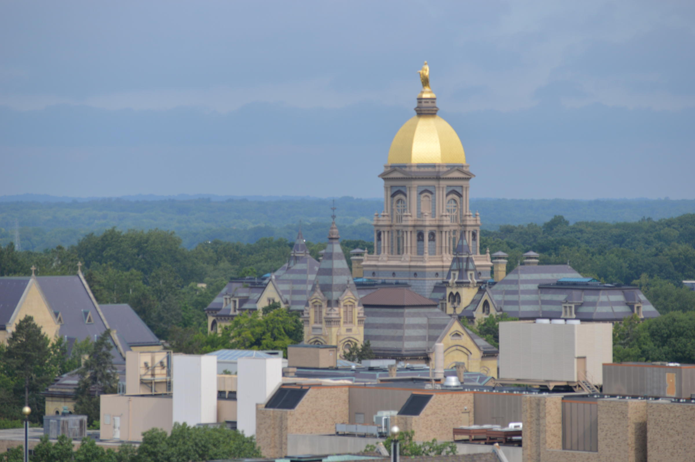 The University of Notre Dame golden dome surrounded by other campus buildings.