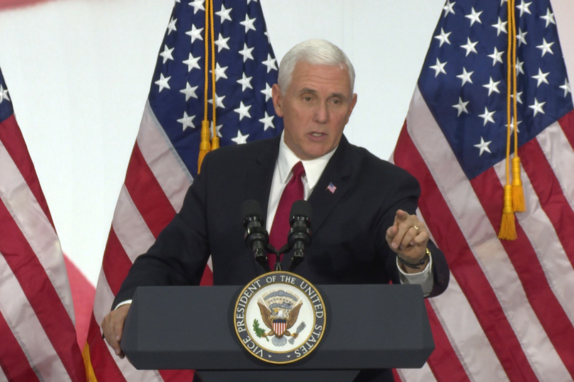 VP Mike Pence in front of three U.S. flags