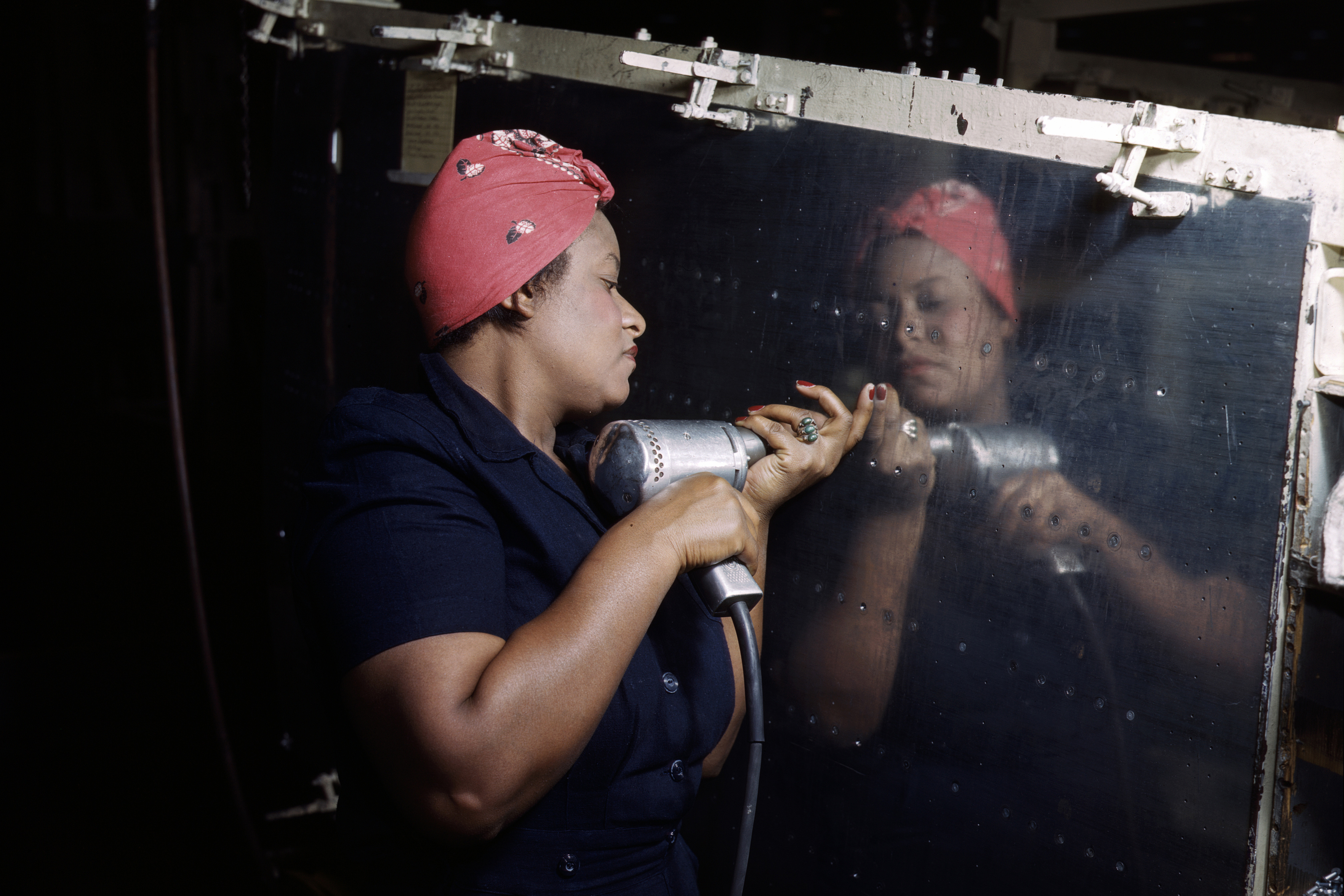 """A real-life """"Rosie the Riveter"""" operating a hand drill at Vultee-Nashville, Tennessee, working on an A-31 Vengeance dive bomber."""