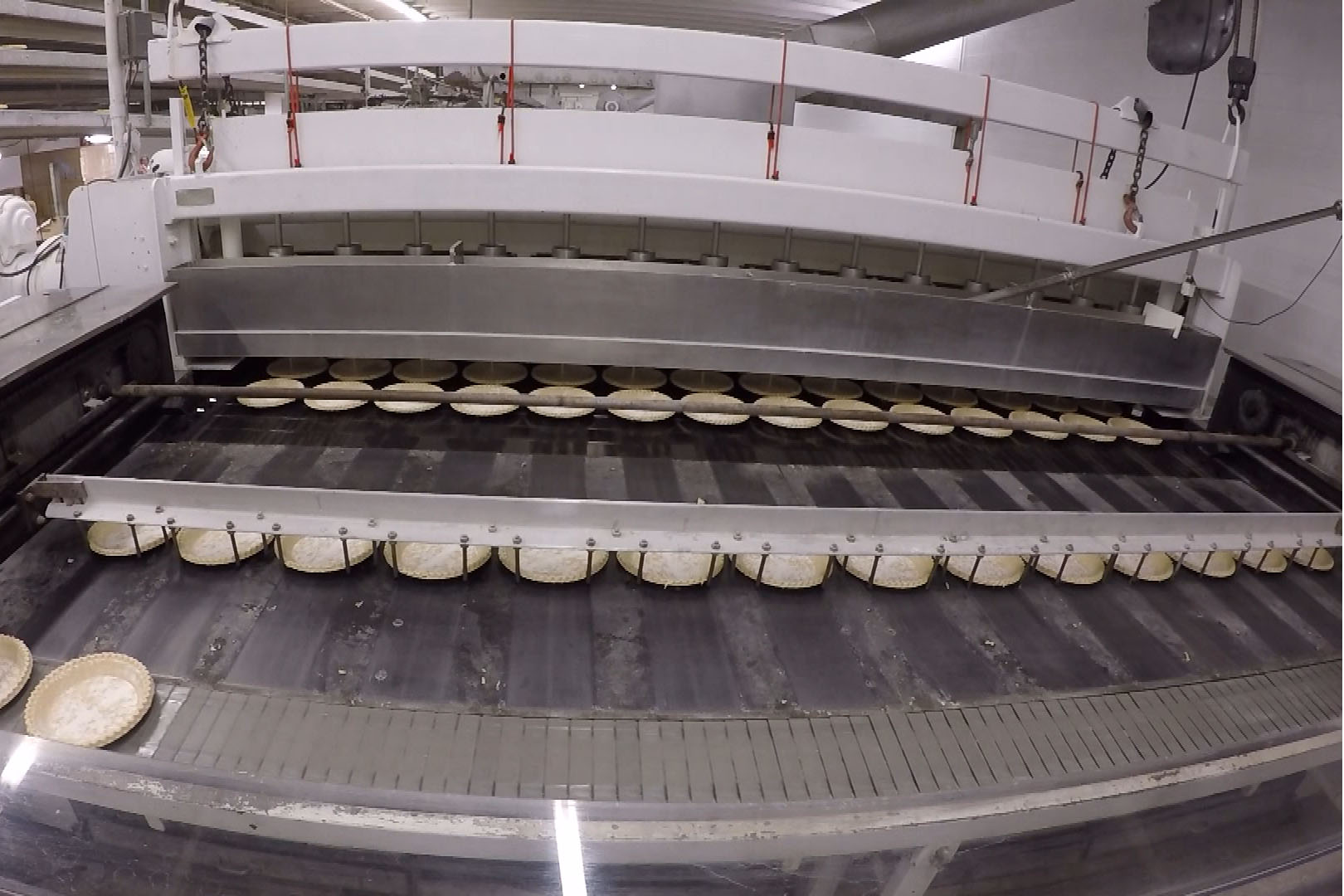The pies are lined up in rows of 14, then pushed into the oven. A machine pours sugar cream pie filling into the shells as they enter the oven.