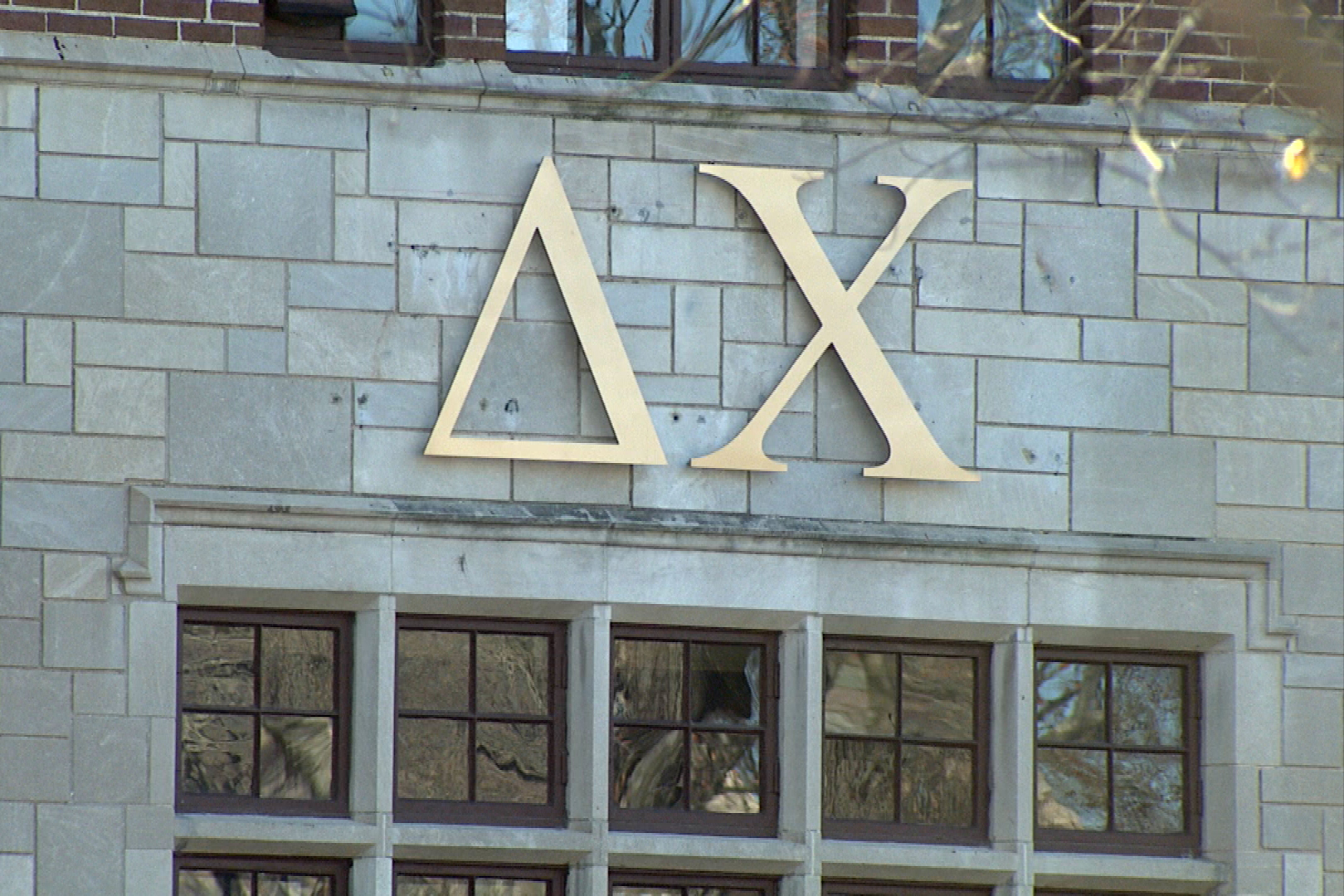 Fraternity letters affixed to the brick exterior of a frat house.