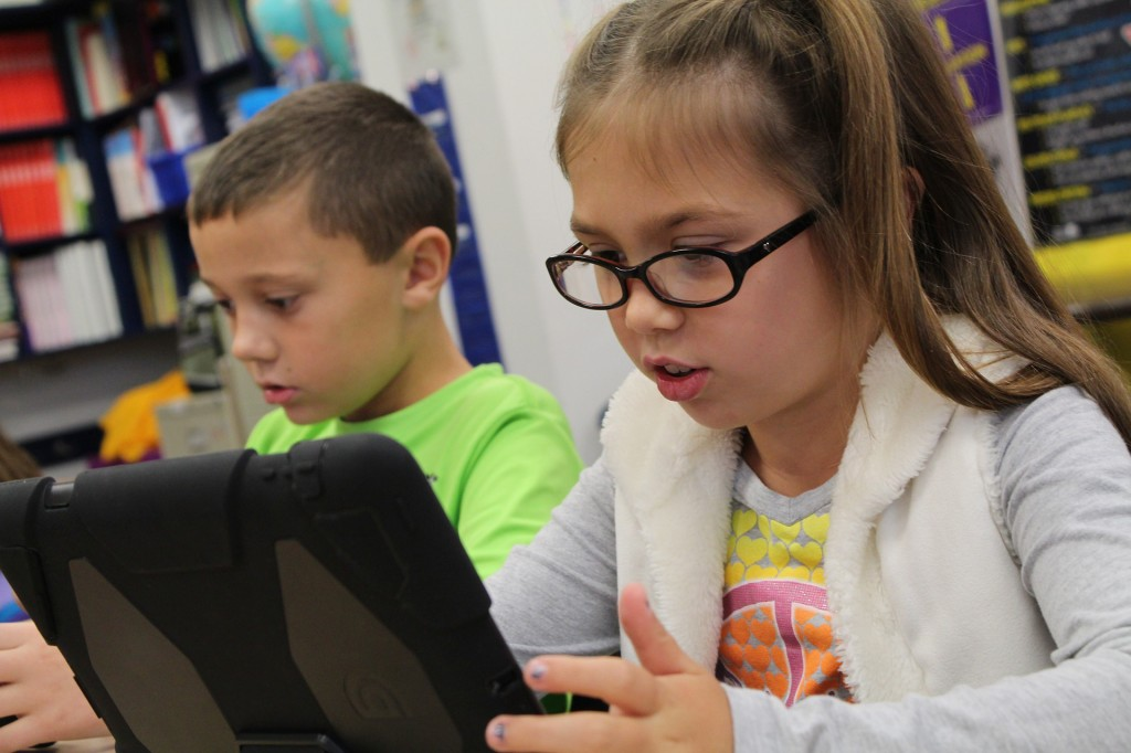 Two children sitting at a school table. The one in the foreground has long brown hair and glasses and is using a tablet computer. The one in the background has short brown hair and is wearing a green shirt.