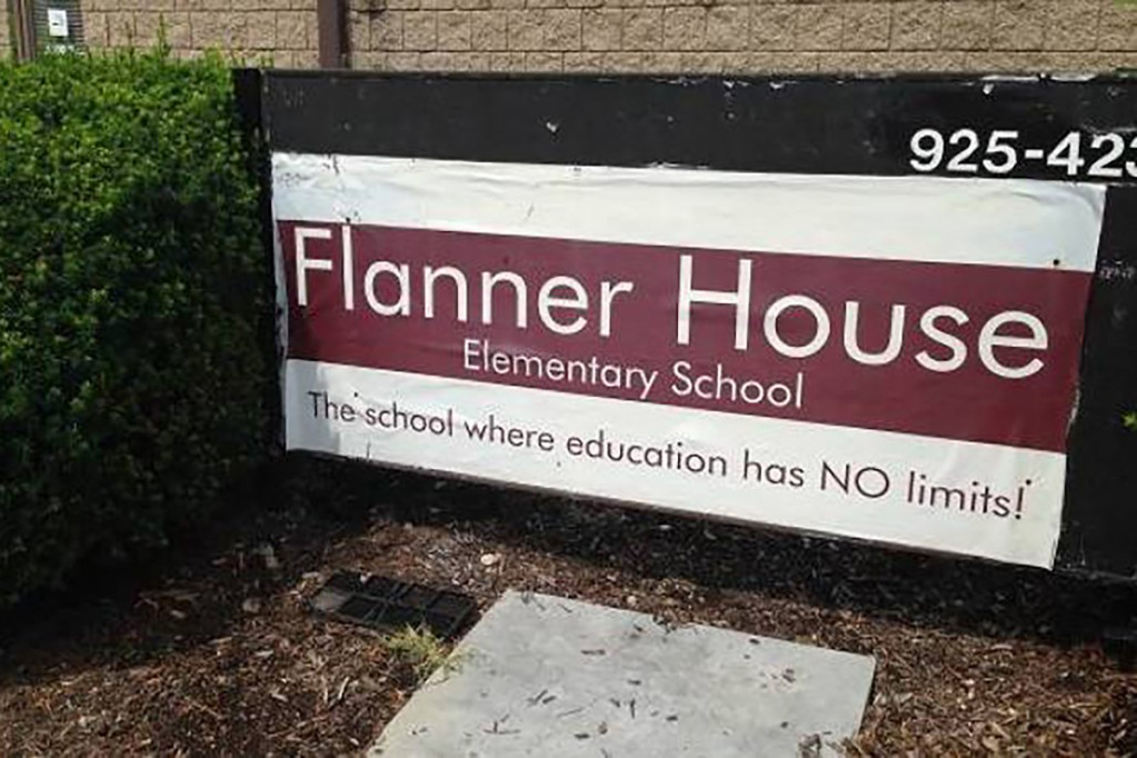 """Sign outside of Flanner House Elementary, which reads """"The school where education has no limits!"""""""