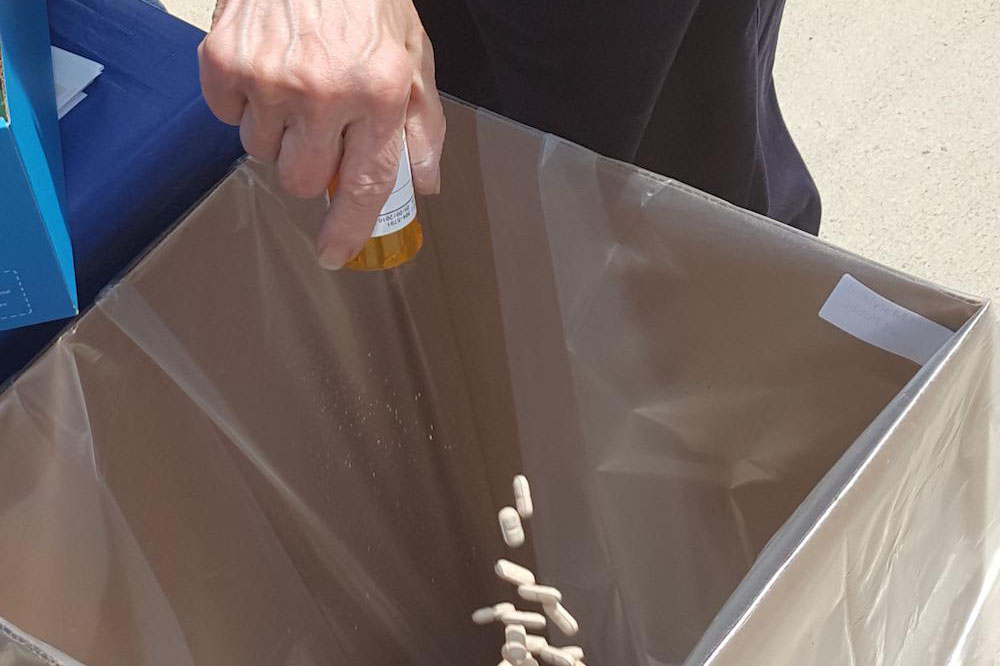 A hand dumping white pills into a trash receptacle.