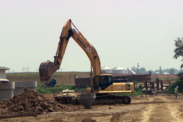 A construction truck moves dirt along a section of what will become I-69.