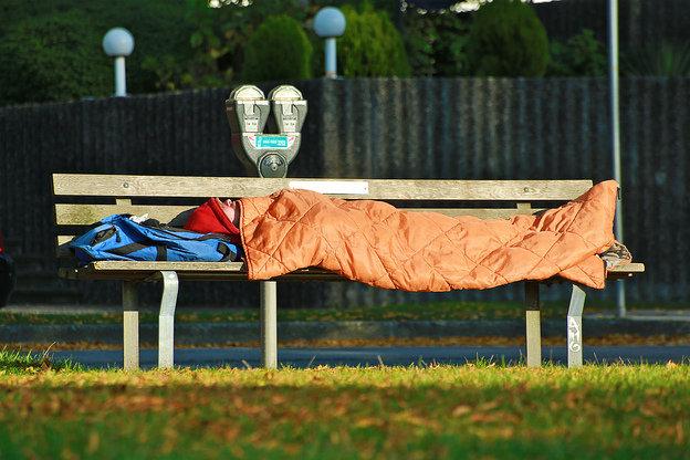 Homeless man sleeps on a bench.