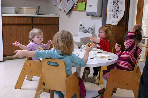 Students enjoy snack time at daycare.