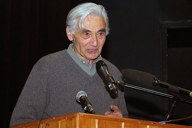 Howard Zinn speaks at a podium.