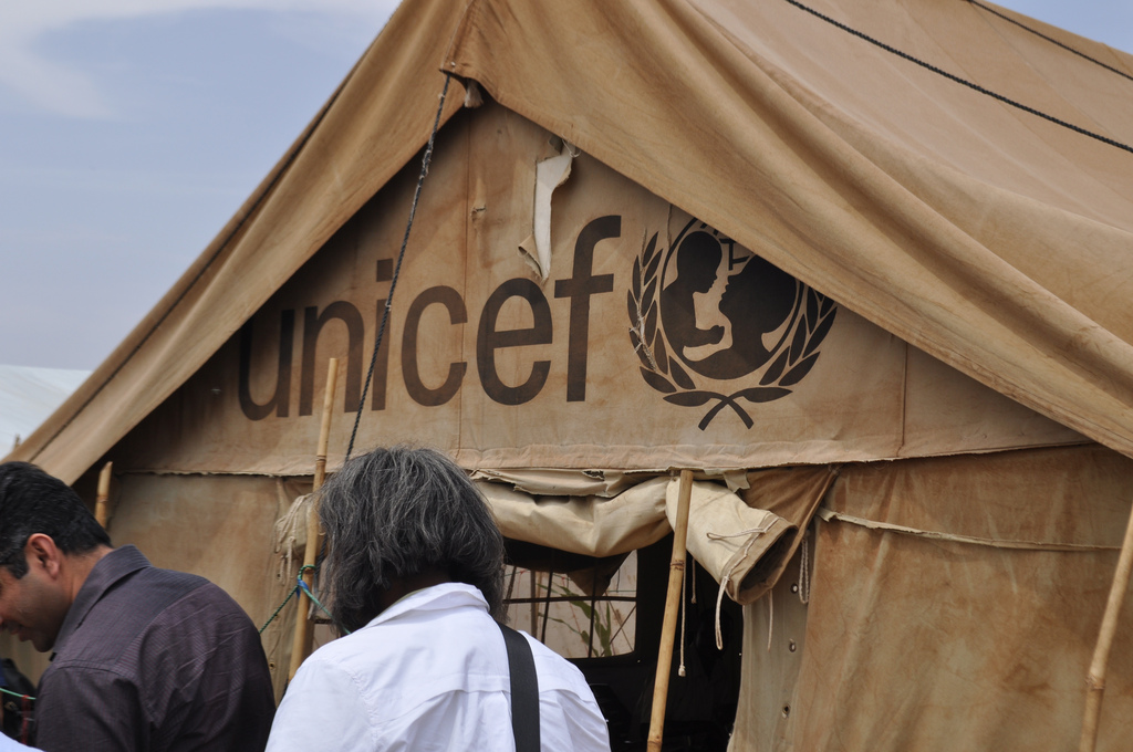 "Two people stand in the foreground of a brown tent that says ""UNICEF"""