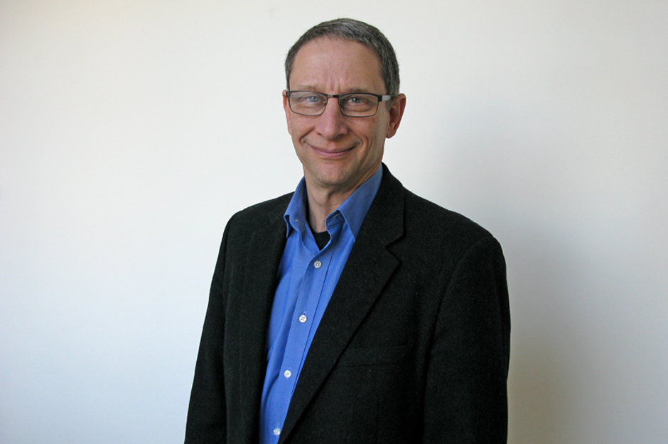 David Finkel in blue shirt open at the neck and black blazer, glasses