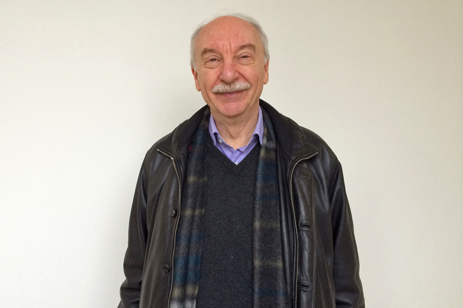 Gerd Gigerenzer in black sweater, plaid scarf, and black leather jacket