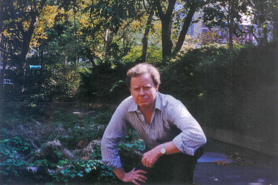 Larry Lockridge outside, in an open-necked shirt, crouching