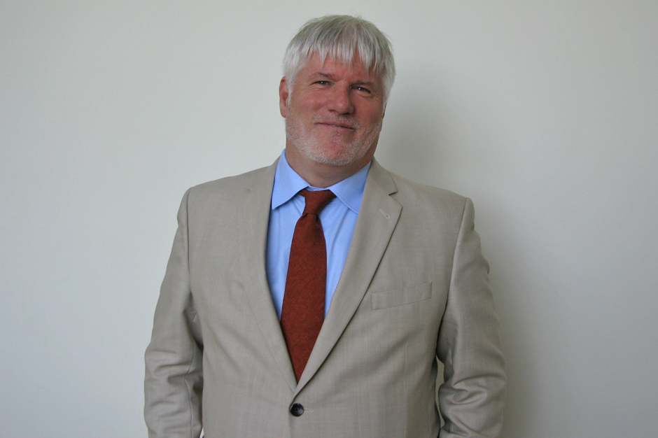 Thomas French in off-white suit, light blue shirt, red tie, semi-smiling
