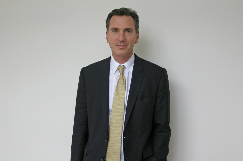 Lee A. Feinstein in black suit, gold tie