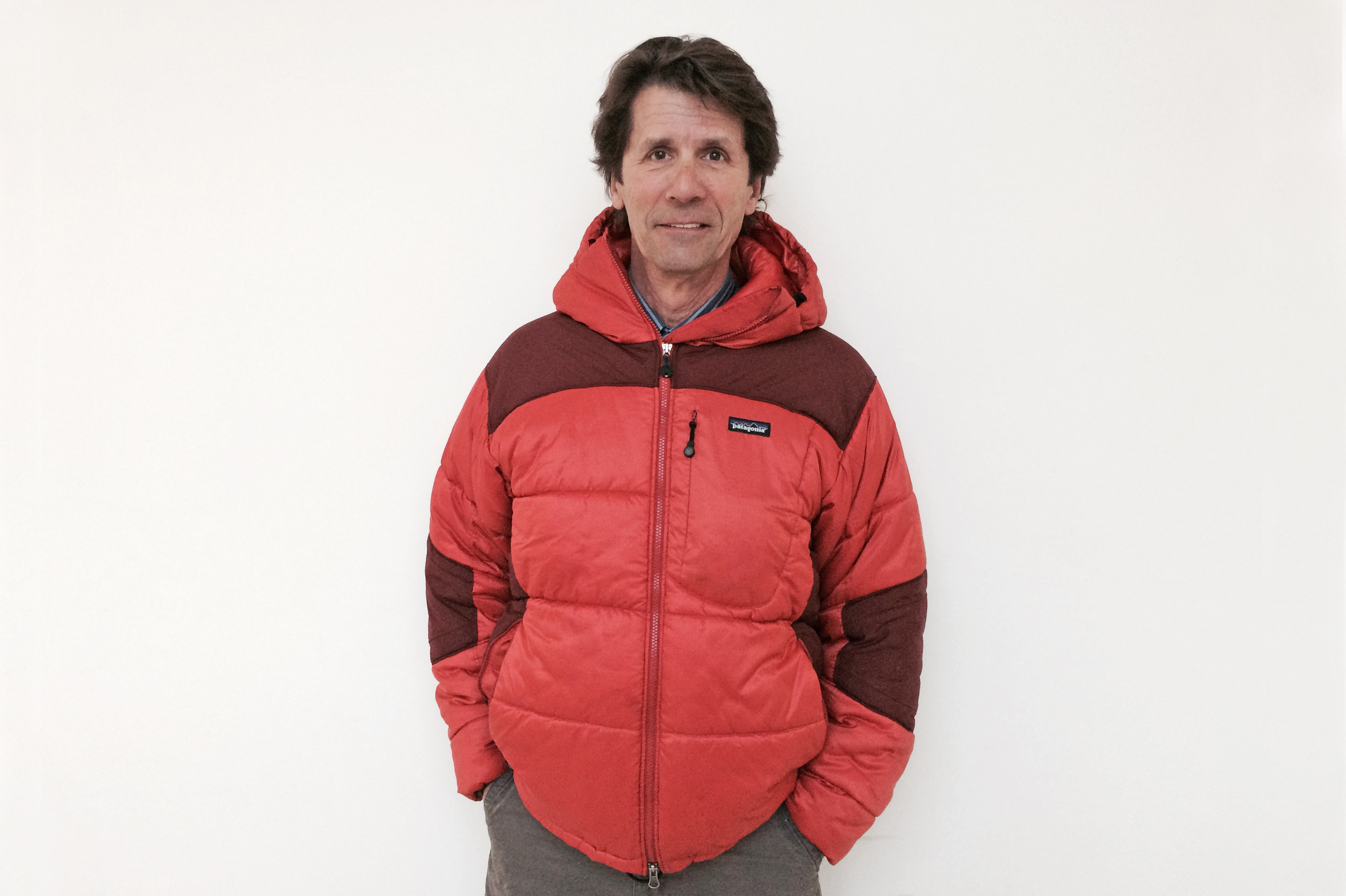 James Balog with hands in pants pockets, wearing zipped-up red parka