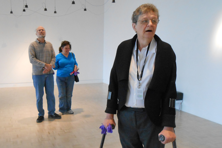 Marian Pettengill, using braces, leads a low-vision tour in gallery with white walls and ceiling at the Indianapolis Museum of Art. Art objects hang from the ceiling.  Tour participants Rhett Salisbury and Mary Stores stand in the background.