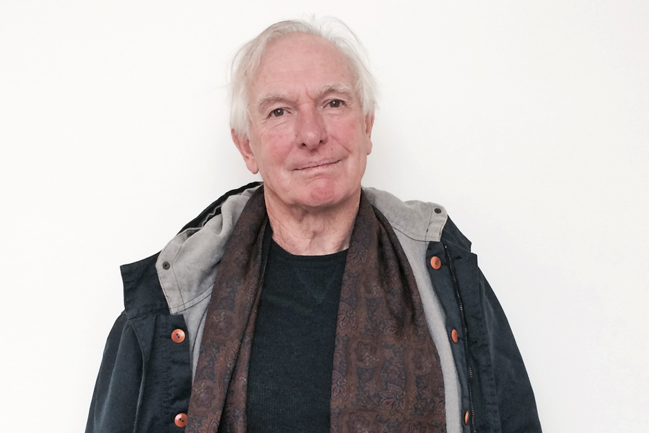 Peter Weir, white-haired, head tilted a little, in parka over black shirt and brown scarf