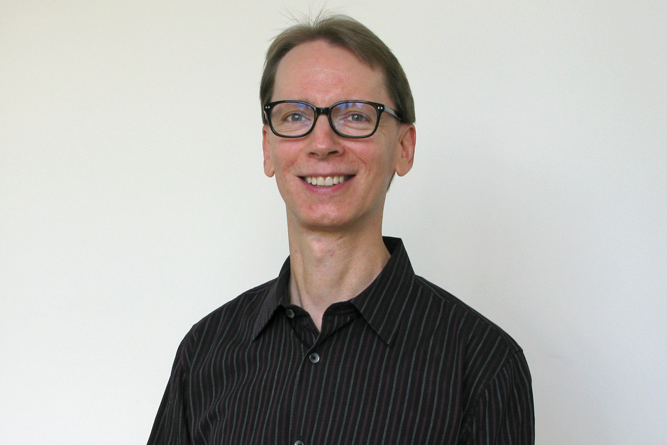 Luke Gillespie with short hair, black hornrimmed glasses, black-and-gray striped shirt open at the collar.