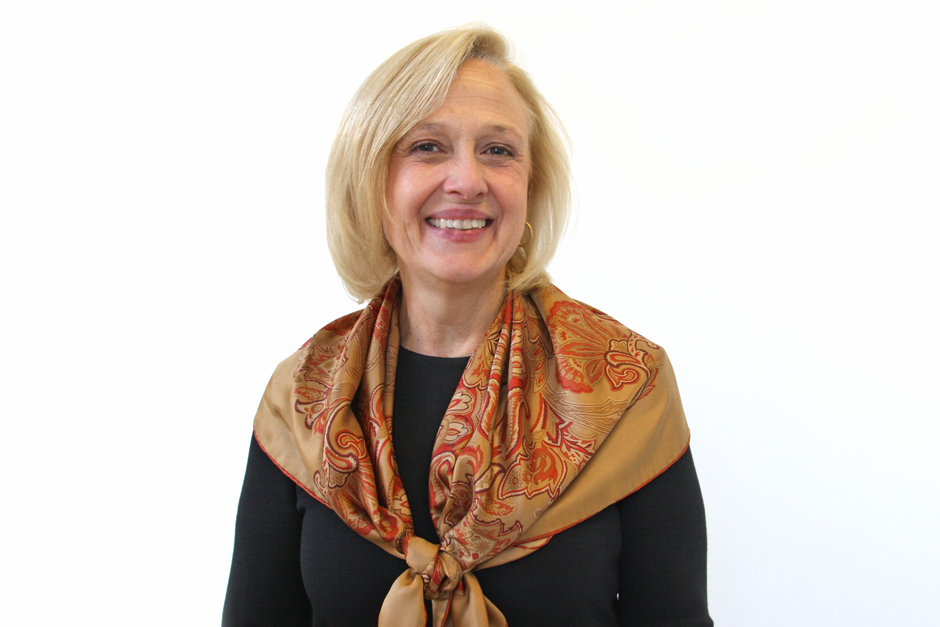 Paula Kerger in black top and scarf draped over shoulders, smiling.
