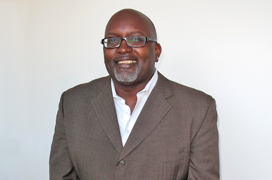 Eric Deggans, smiling, in glasses, open-necked white dress shirt, gray suit jacket, glasses