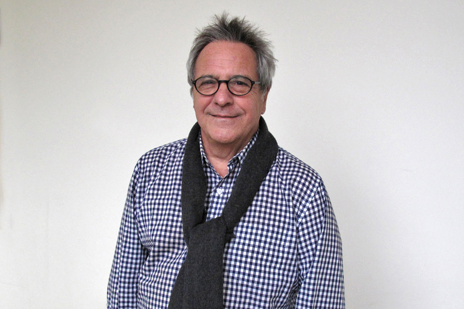 David Anspaugh in glasses, blue-and-white checked shirt, navy blue sweater draped around his shoulders