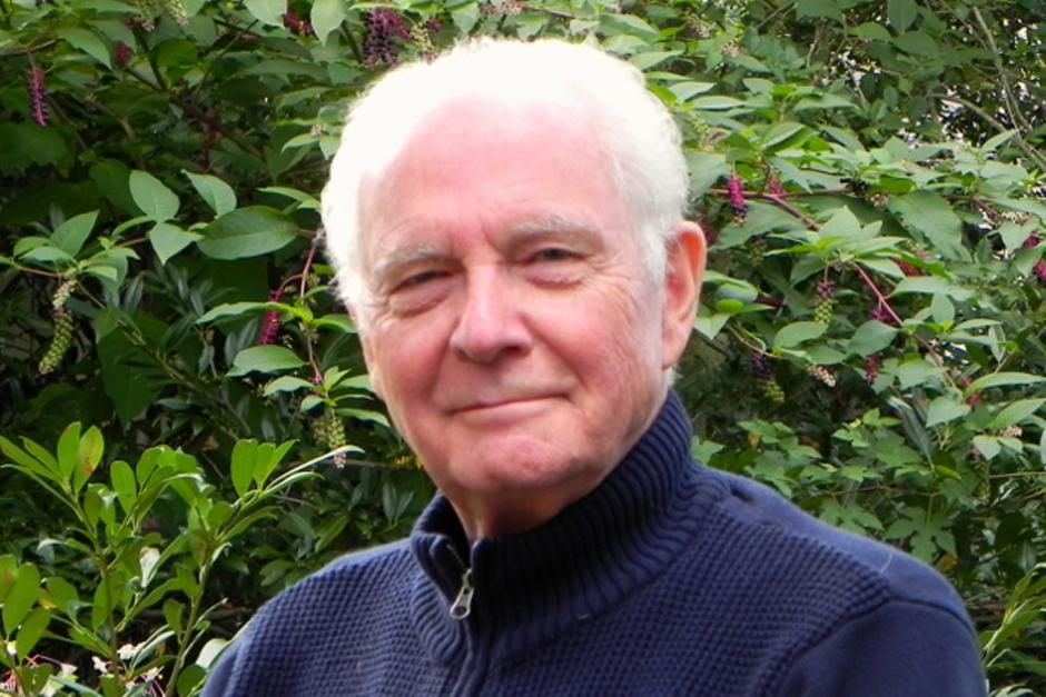 Bill Siemering outdoors, in a blue, zippered sweater