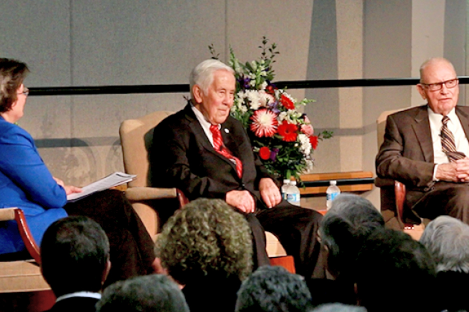 USI President Dr. Linda L.M. Bennett, Senator Richard G. Lugar, and former Congressman Lee H. Hamilton seated on stage with heads of audience members in foreground.