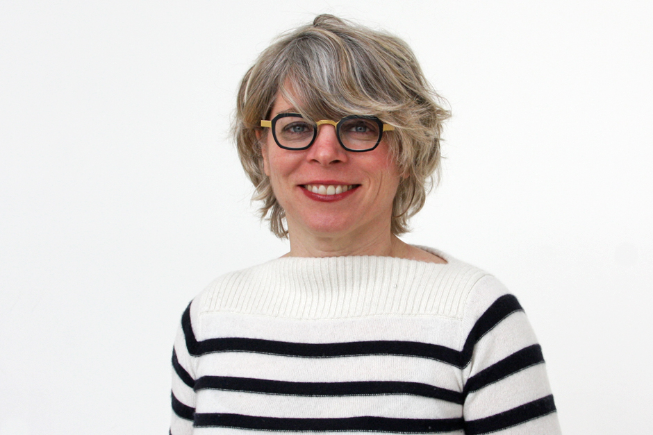 Jill Lepore wearing white sweater with black horizontal stripes, her hair covering forehead and touching black horn-rimmed glasses.