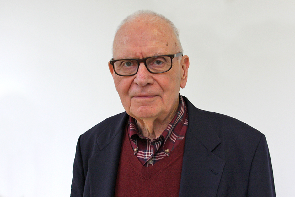 Lee Hamilton wearing glasses, dressed in red checked shirt, maroon sweater, and black suit jacket.