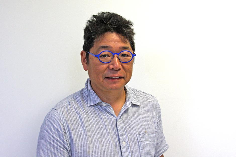 Osamu James Nakagawa in wearing round, blue-framed glasses and short-sleeved shirt.