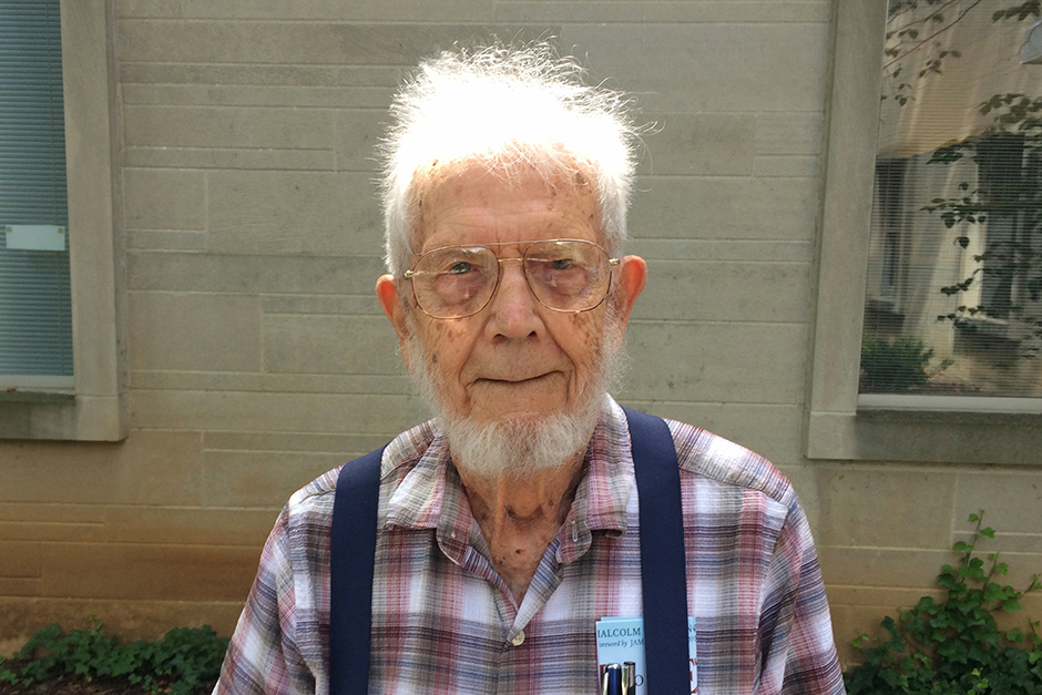 Mac Fleming: white hair, wireframe glasses, in checked flannel shirt with navy suspenders, pens and paper in breast pocket.