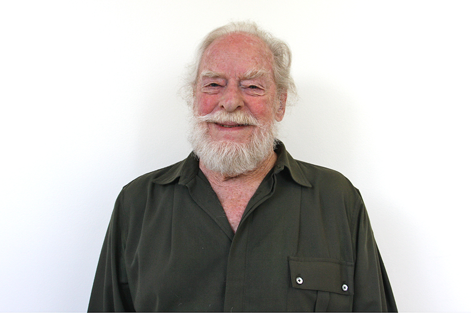 James Alexander Thom in black shirt, gray beard and mustache, smiling