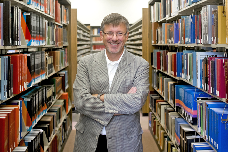 Michael Adams in glasses, black-and-white checked jacket over white dress shirt open at the collar, poses smiling and with arms crossed between stacks of books in the reference section of the Herman B Wells Library on Tuesday, July 26, 2016.