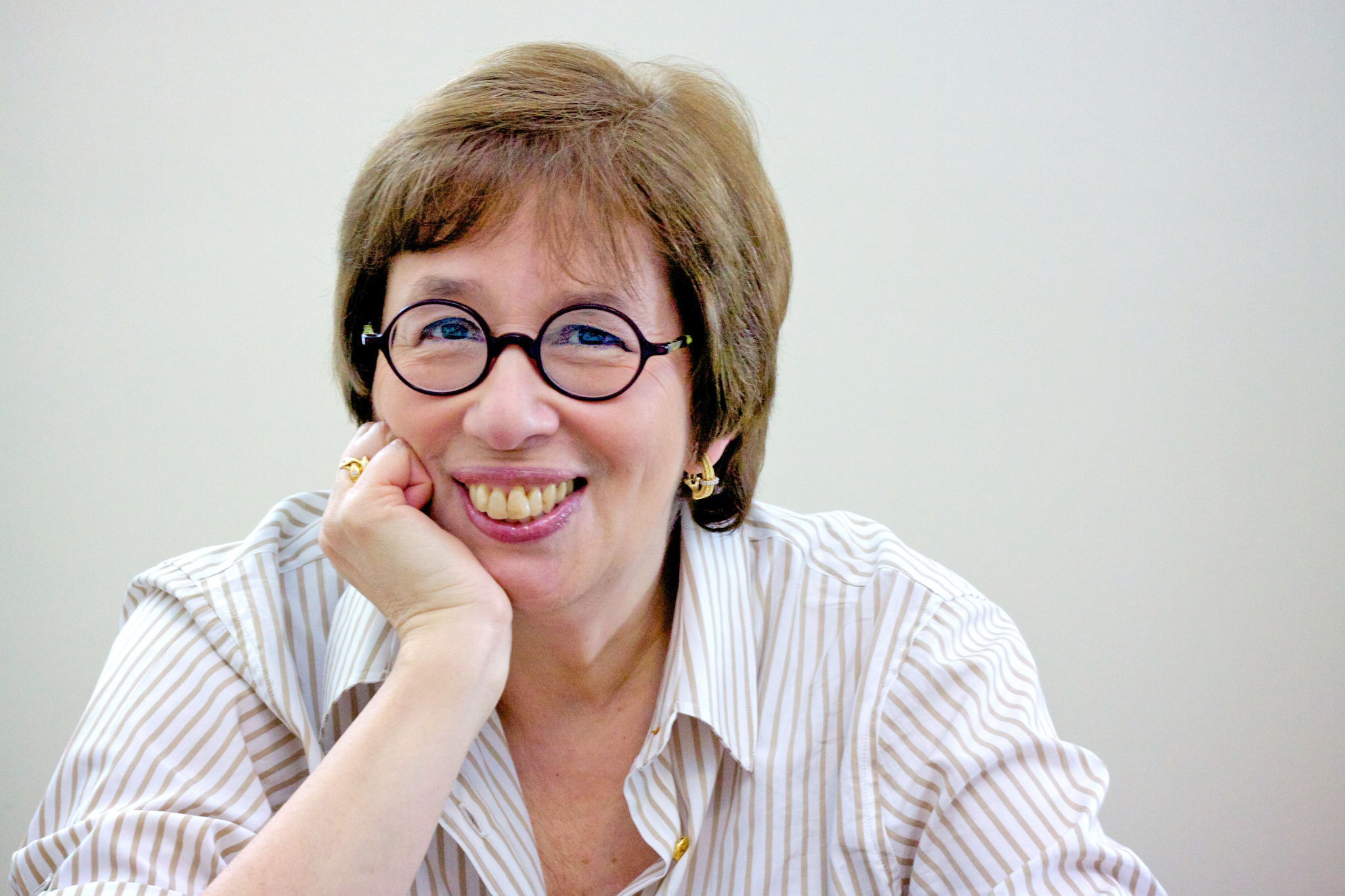 Linda Greenhouse, sitting with chin resting on right palm, wearing round-framed glasses, open-necked striped shirt, smiling.