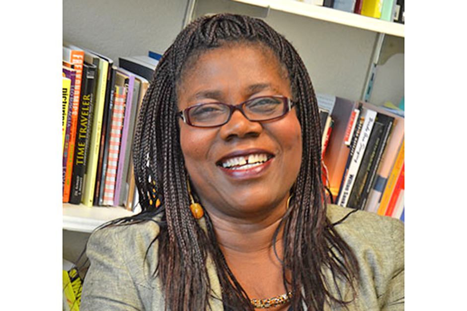 P. J. Wesley, smiling, in glasses with hair in braided cornrows, books in bookshelf behind her.