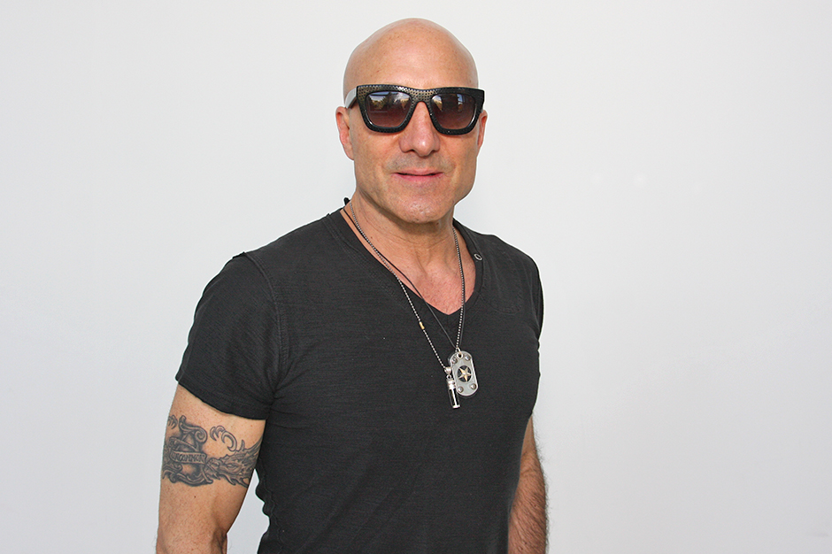 Kenny Aronoff in dark sunglasses, black T-shirt, with tattoo on right arm.