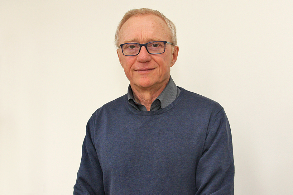 David Grossman, wearing glasses, in a dark blue sweater over a gray striped shirt unbuttoned at the neck.