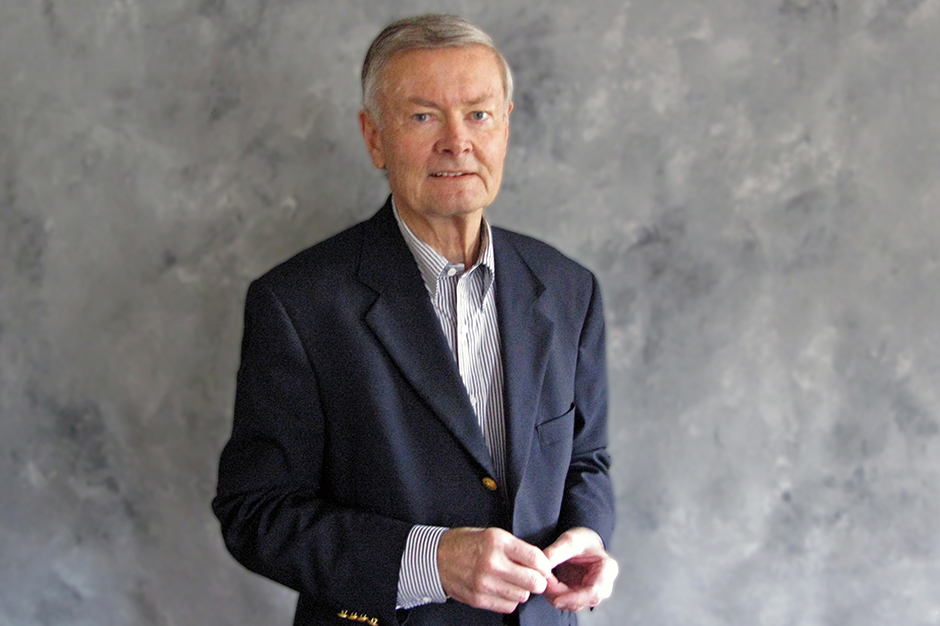 Dick Bishop against studio backdrop, wearing navy blazer, blue-and-white vertically-striped shirt open at neck